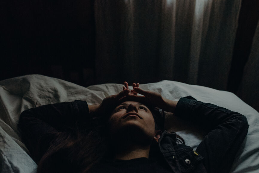 Woman laying on the bed looking at the ceiling