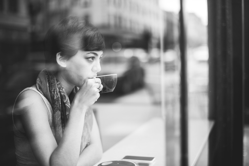 Woman reflecting over a cup of Coffee