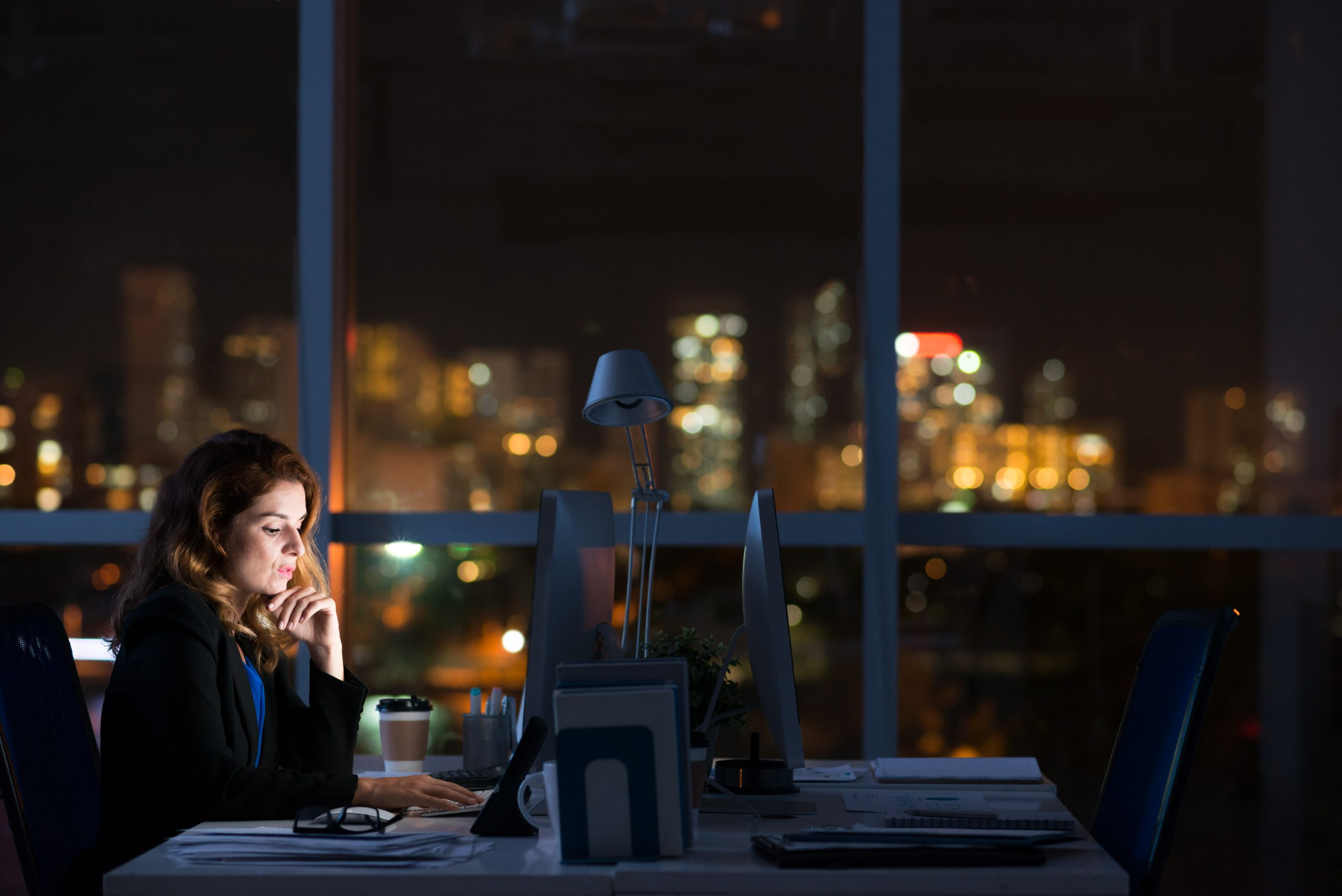 Woman working overtime at her desk at night